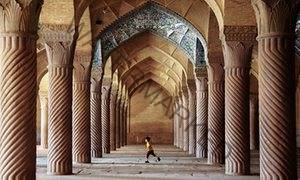 A boy runs between pillars at the Vakil mosque in Shiraz, Iran.